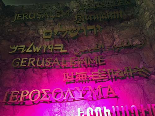 the word Jerusalem, displayed on a wall in different languages, lit up by pink lighting.