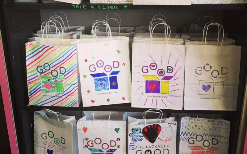 Paper bags decorated by children with the word Good printed across the front.