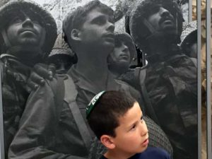A boy stands in front of a poster of soldiers at the Western Wall in the aftermath of the Six Day War